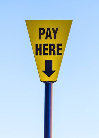 inform information: A yellow and blue, triangular sign informing people to Pay Here with an arrow pointing down to a ticket machine with a blue sky background.