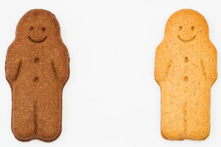 niños diferentes razas: Dos hombres de pan de jengibre blancos y negros en un fondo aislado con el espacio de la copia que representa racial, la igualdad, la diversidad y la armonía. Foto de archivo