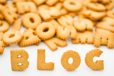 The word BLOG spelled out of alphabet shaped cookies or biscuits and on an isolated white background Stock Photo