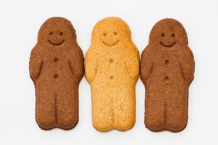 niños diferentes razas: Una fila de hombres de pan de jengibre blancos y negros que sonríe y que parece feliz representando la armonía racial, la igualdad y la diversidad en un fondo blanco aislado. Foto de archivo