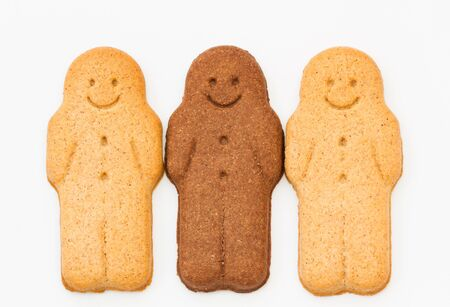 A row of black and white Gingerbread Men smiling and looking happy representing racial harmony, equality and diversity on an isolated white background. Stock Photo