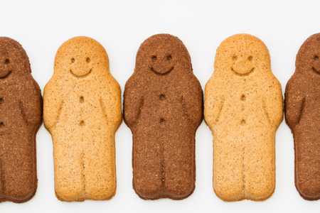gingerbread man: A row of black and white Gingerbread Men smiling and looking happy representing racial harmony, equality and diversity on an isolated white background. Stock Photo