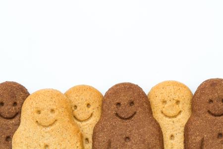 niños diferentes razas: Una fila de hombres de pan de jengibre en blanco y negro sonriendo y mirando feliz en la parte inferior del marco que representa la armonía racial, la igualdad y la diversidad en un fondo blanco aislado.