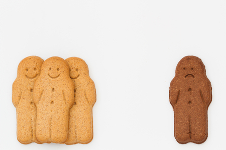 An unhappy black gingerbread man segregated from a group of happy, white gingerbread men on an isolated white background representing racial division and segregation.