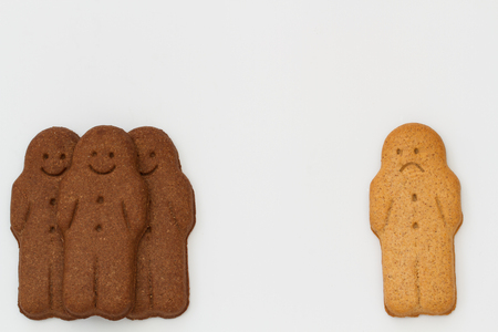 niños diferentes razas: An unhappy white gingerbread man segregated from a group of happy, black gingerbread men on an isolated white background representing racial division and segregation.