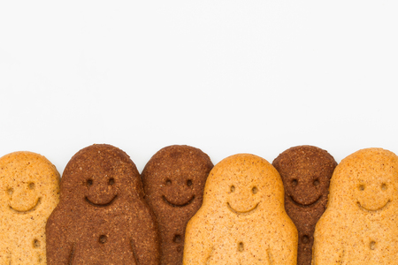niños diferentes razas: A row of black and white Gingerbread Men smiling and looking happy at the bottom of the frame representing racial harmony, equality and diversity on an isolated white background.