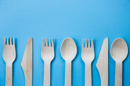A variety of recyclable wooden cutlery including knife, fork and spoon on a blue background with copy space