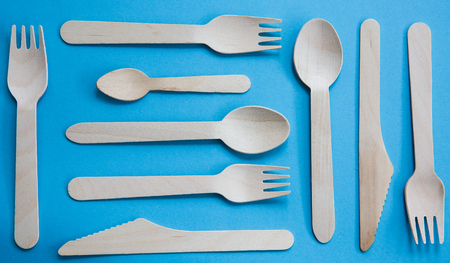 A variety of recyclable wooden cutlery including knife, fork and spoon on a blue background Stock Photo