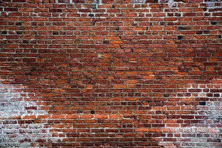A full frame background of a rough and textured brick wall with visible wear and tare and copy space