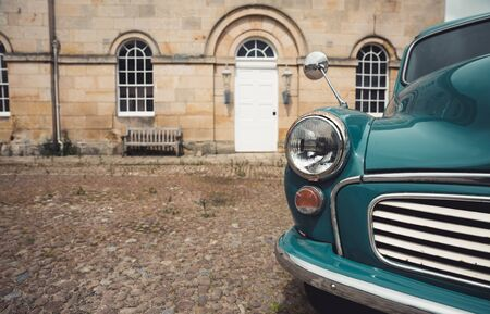 A close up of a classic blue, vintage Morris Minor Panel Van or car in old fashioned city surroundings with copy space Archivio Fotografico
