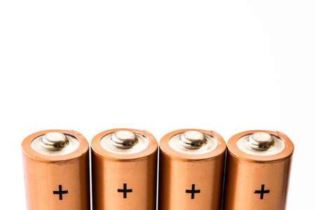 A close up of the positive terminals of disposable AAA batteries on a white background with copy space