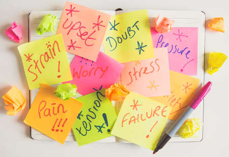 A concept of a person or business showing anxiety and doubt with sticky notes full of negative comments about doubt, stress, anxiety and pain