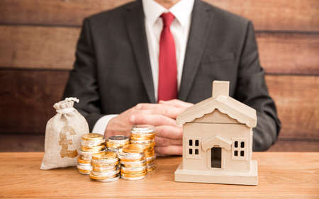 A housing concept of the cost and price of homes with a real estate agent or mortgage broker sitting with a property and money to represent fees, mortgage and house prices. Banque d'images