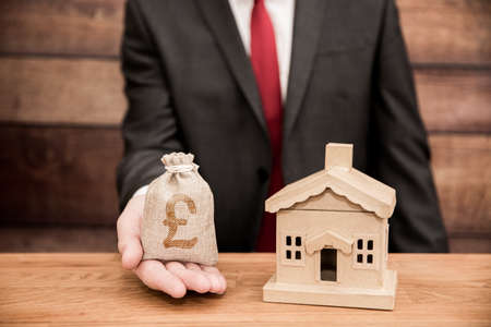 Real estate agent concept showing the cost of house prices, homes, mortgages and home insurance with an estate agent holding a bag of money next to a new house