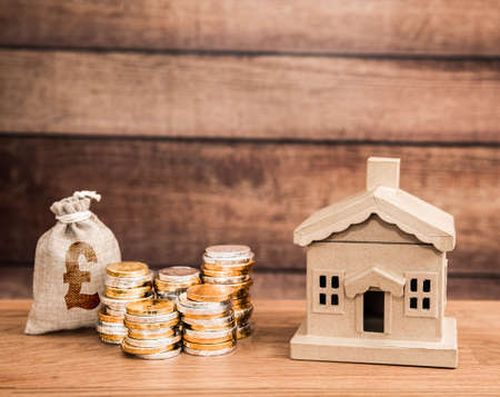 A housing property concept with a home and stacks of money representing family savings and cost of housing or rental with copy space Banque d'images