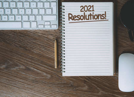 A desk with a notebook and computer with the business planning for the future and 2021 resolutions