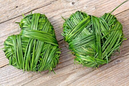 Two hearts of grass on wooden background Stock Photo