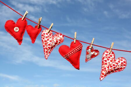 Handmade hearts of scrim hanging on line , an the background of blue sky Stock Photo