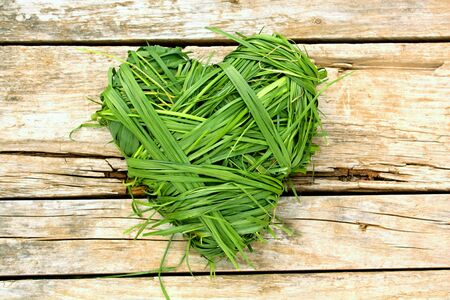 Heart shaped from green grass on wooden background
