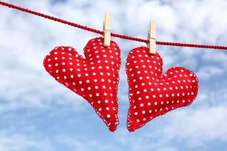 Handmade hearts of scrim hanging on line , on the background of blue sky