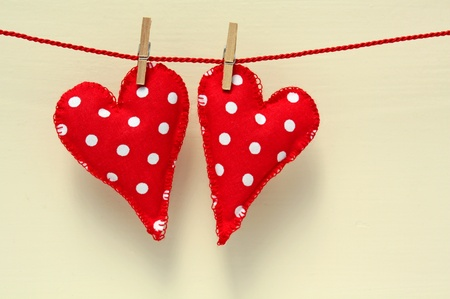 Handmade hearts of scrim hanging on line , an the background painted wooden wall