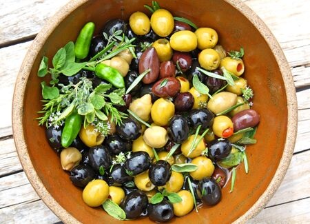 Marinated various olives in bowl Stock Photo