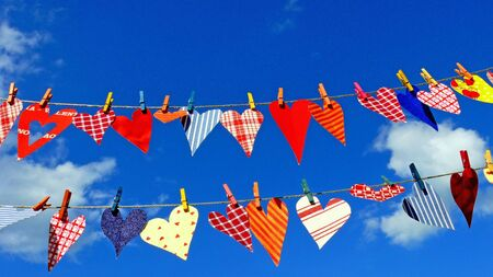 colorful hearts hanging on lines, on the backdrop of a blue sky photo