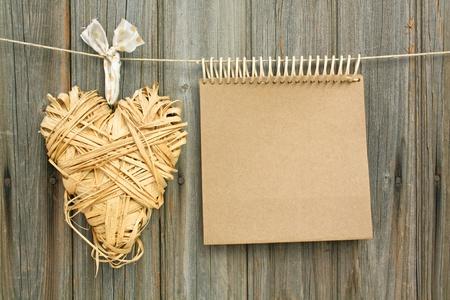 jegyzettömb szív készült Hayl akasztás előtt, fából készült fal Stock fotó
