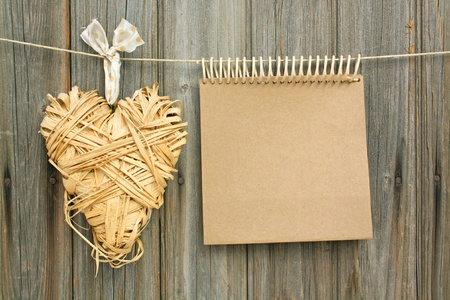 shaped: notepad with a heart made ​​of hayl hanging in front of wooden wall