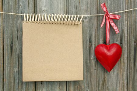 notepad with a heart made ​​of sheet metal hanging in front of wooden wall photo