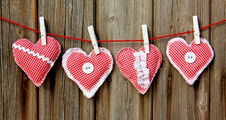 four handmade hearts hanging on wooden wall photo