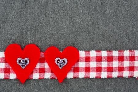 felt: folk background with red felt hearts and plaid ribbon