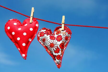 Két kézzel varrott szív készült piros ruhát lóg pórázon Stock fotó