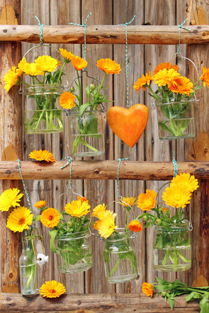 marigolds posy and a love heart hanging on a wood ladder