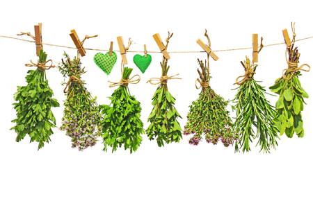 various fresh herbs and two hand-sewn cloth hearts hanging on a linen
