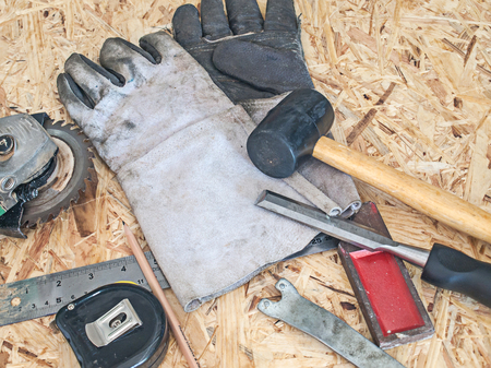 Carpenter tool, gloves, hammer, chisel, tape, grinder with saw blade. photo