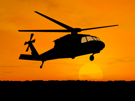 Silhouette of helicopter over sunset photo