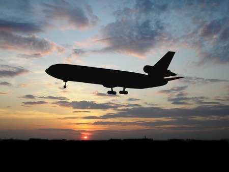 Silhouette of airplane over sunset photo