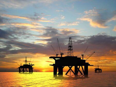 Oil rig silhouette over orange sky Stock Photo