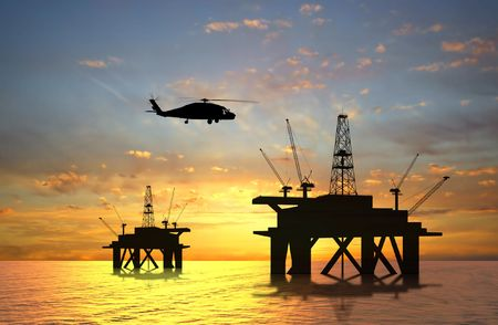 construction platform: Oil rig silhouette over orange sky Stock Photo