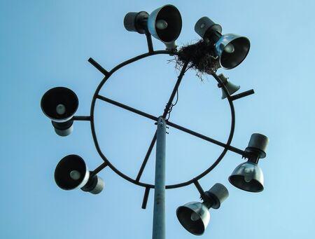 under spotlight and speaker pole photo