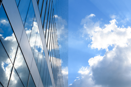 Office building details reflecting blue sky and clouds in windows