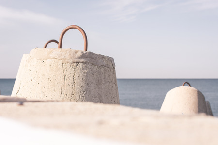 Concrete breakwaters in the foreground with sea on background Stock Photo