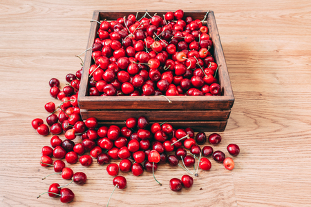 Sweet cherries in the wooden box on the wooden table
