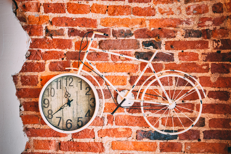 Bicycle clock on the red bricks wall