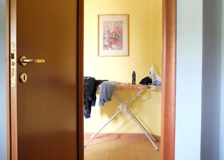 Ironing board behind a door photo