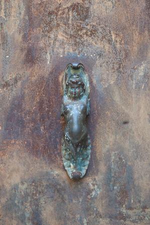 Oud ijzer handvat in de vorm van een vrouw vast te zitten in een oude poort die wordt gebruikt om aan te kloppen