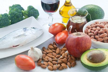 10 foods to lower cholesterol : tea , avocado , fruit , vegetables,walnuts , almonds , fish , wine
