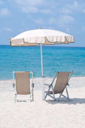 blu sky: two deckchairs on the beach under an umbrella