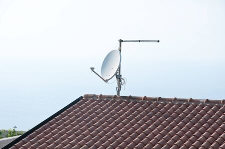 antena parabolica: antena parab�lica de televisi�n en un techo con fondo de mar, Italia